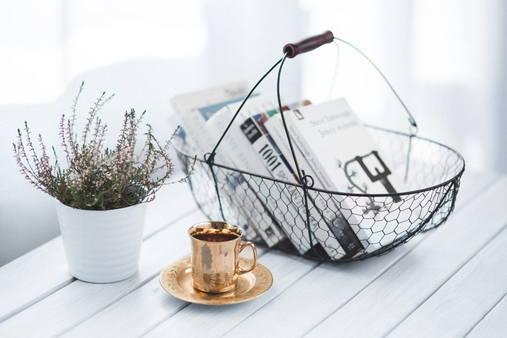black wire basket with books beside gold tea cup set and plant