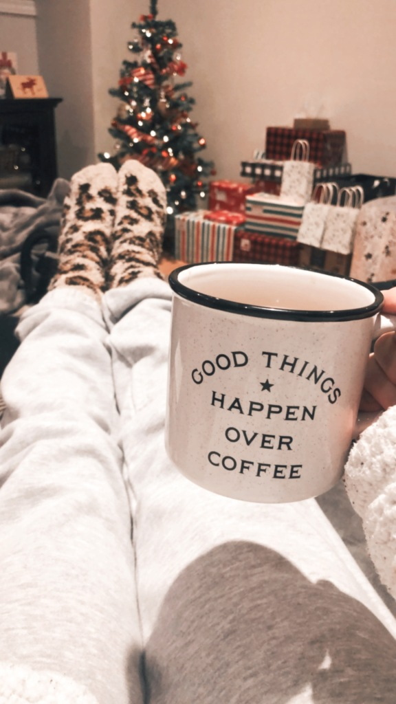 good things happen over coffee mug with Christmas tree and presents in background