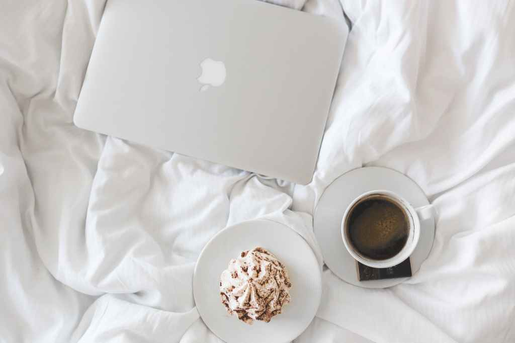 coffee and a treat with laptop on bed- flat lay image